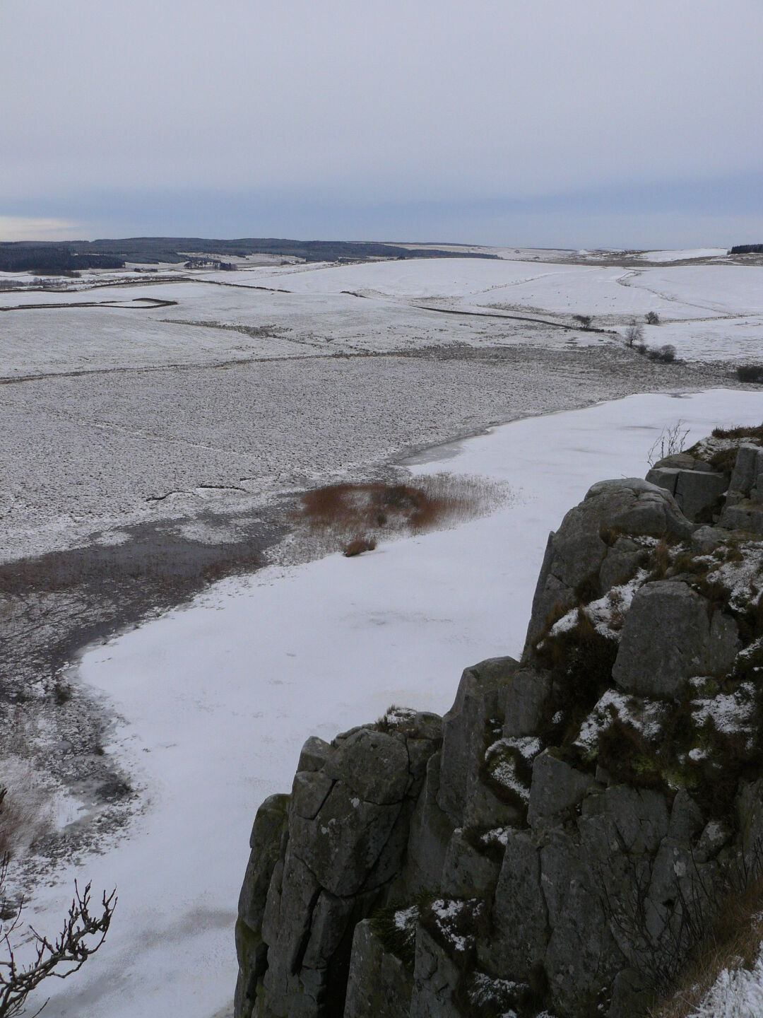 Frozen lake Crag Lough beneath the cliffs.