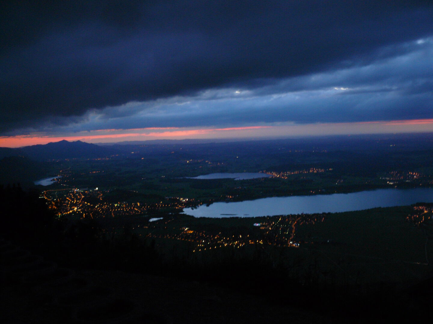 The Forggensee and city of Füssen in the evening, as seen from Tegelberghaus.